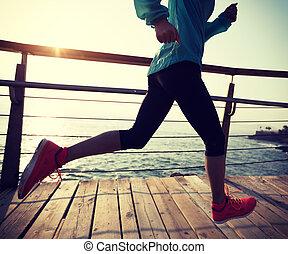 fitness sporty female runner running on seaside boardwalk