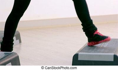 Fitness. Step aerobics closeup - Young women doing step...