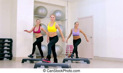 Fitness. Step aerobics - Young women doing step aerobics