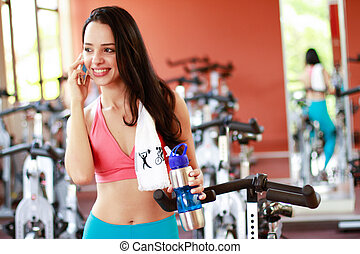 fitness - Woman talking on cell in fitness