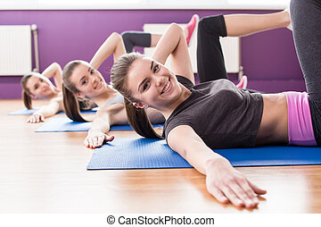 Fitness - Group of active smiling women are training in...