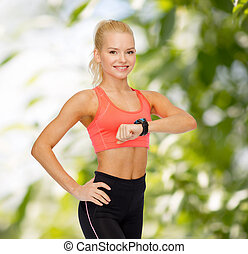smiling woman with heart rate monitor on hand - fitness,...