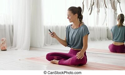 woman with smartphone at yoga studio - fitness, technology...