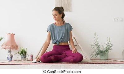 woman with smartphone meditating at yoga studio - fitness,...