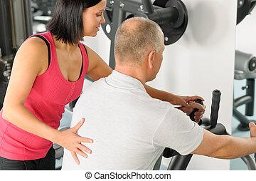 Active man watch personal trainer adjust machine level at gym