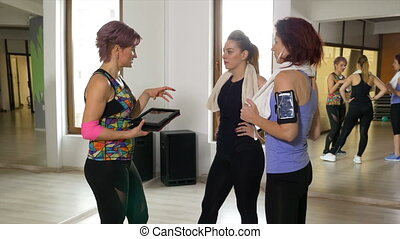 Fitness trainer at the gym showing workout schedule using a digital tablet pc computer to women