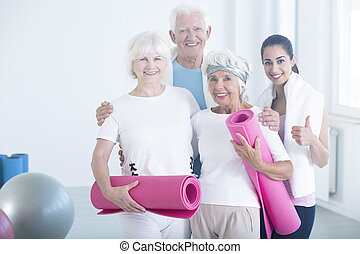 Fitness trainer congratulating elderly people - Smiling ...