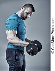 Fitness trainer doing biceps workout in the studio