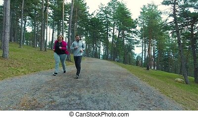 Fitness trainer in park running with attractive overweight woman.