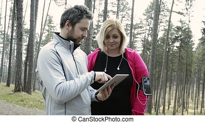 Fitness trainer in park talking to attractive overweight woman.