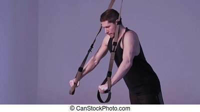 Fitness trainer video instructing exercising suspension training trx on light purple background. Fitness concept. Sports concept. Toned footage. Prores 422.