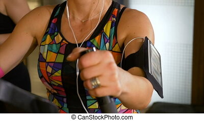 Fitness trainer with headphones and tracker gadget working out on the stepper