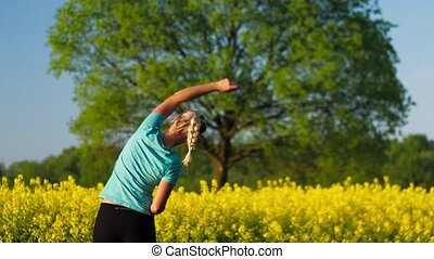 Fitness training of an gild at open air. Blooming fresh yellow rapeseed field with an big oak tree in background