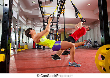 Fitness TRX training exercises at gym woman and man -...