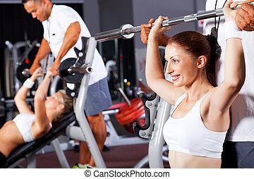 fitness, vrouw, met, persoonlijke trainer, in, gym