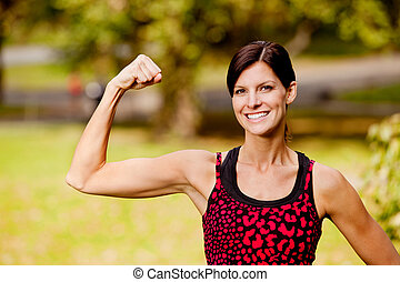 A pretty fitness model flexing her bicep