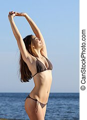 Fitness woman body posing standing on the beach