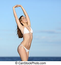 Fitness woman body with white bikini posing on the beach
