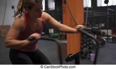 Fitness woman doing air bike workout in gym