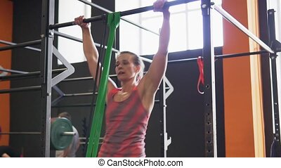 Fitness woman doing bar muscle-up exercise in gym