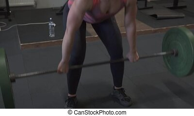 Fitness woman doing barbell clean and jerk workout in gym