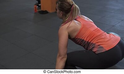 Fitness woman doing barbell snatch training in gym