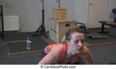 Fitness woman doing barbell snatch workout in gym