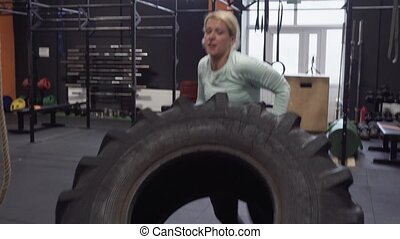 Fitness woman doing big tire flips exercise during functional training