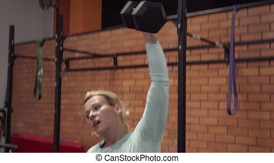 Fitness woman doing dumbbell snatch exercise at gym