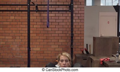 woman doing dumbbell thruster exercise in gym