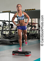 Fitness Woman Doing Exercise On Stepper In Gym - Young Woman...