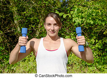 Fitness woman doing exercises with dumbbells