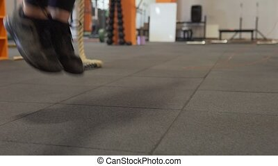 Fitness woman doing jumping rope workout in gym, close-up of legs