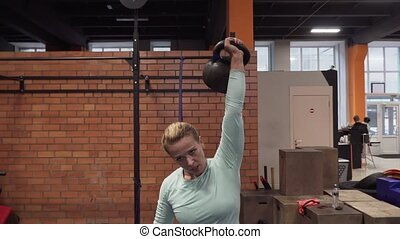 Fitness woman doing kettlebell snatch exercise at gym
