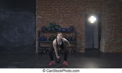 Woman athlete doing kettlebell snatch in the cross-fit gym