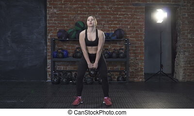 Fitness woman doing kettlebell swings in the gym