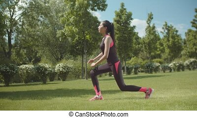 Fitness woman doing lunge exercise on park lawn - Asian ...