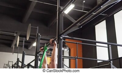 Fitness woman doing muscle-up exercise on gymnastics bar in gym