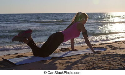 Fitness woman doing push-ups during sports training on beach at sunset