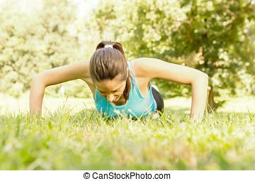 Fitness woman doing push-ups