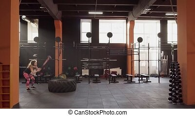 Fitness woman doing sledgehammer swing workout at gym in backlight