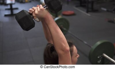 Fitness woman doing weighted sit-ups cross training in gym