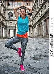 Fitness woman doing yoga near uffizi gallery in florence,...
