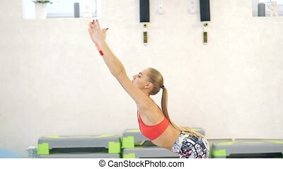 Fitness woman doing yoga stretch in the hall