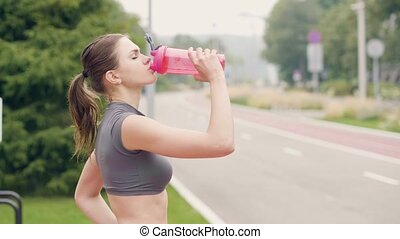 Fitness woman drinking water from bottle while sport training outdoor