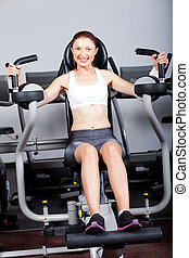 woman exercising with peck deck machine