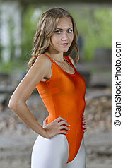 young fitness woman in orange leotard and white shiny pants