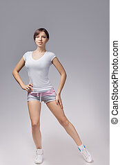 Fitness woman in sport style standing against white background. isolated
