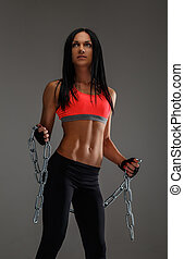 Fitness woman in sportswear holding chain.