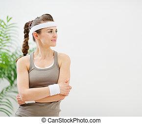 Fitness woman in sportswear looking on copy space